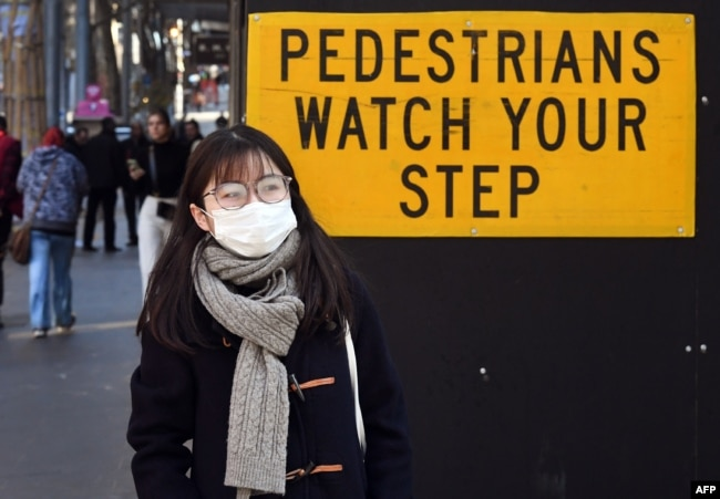 Seorang pejalan kaki berjalan melewati papan peringatan di kawasan pusat bisnis Melbourne, 16 Juli 2020, saat pemerintah Australia mengumumkan bantuan 1,4 miliar dolar AS untuk para pekerja yang terkena dampak Covid-19, 16 Juli 2020.