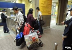 有水貨客在嬰兒車旁掛上裝有多個罐裝及盒裝奶粉的塑膠袋