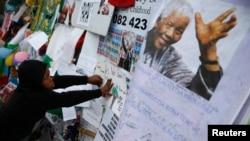 ພວກທີ່ໄປໃຫ້ກຳລັງໃຈ ຢູ່ນອກໂຮງໝໍ ບ່ອນທີ່ອະດີດປະທານາທິບໍດີ Nelson Mandela ກຳລັງຮັບການປິ່ນປົວພະຍາບານ.