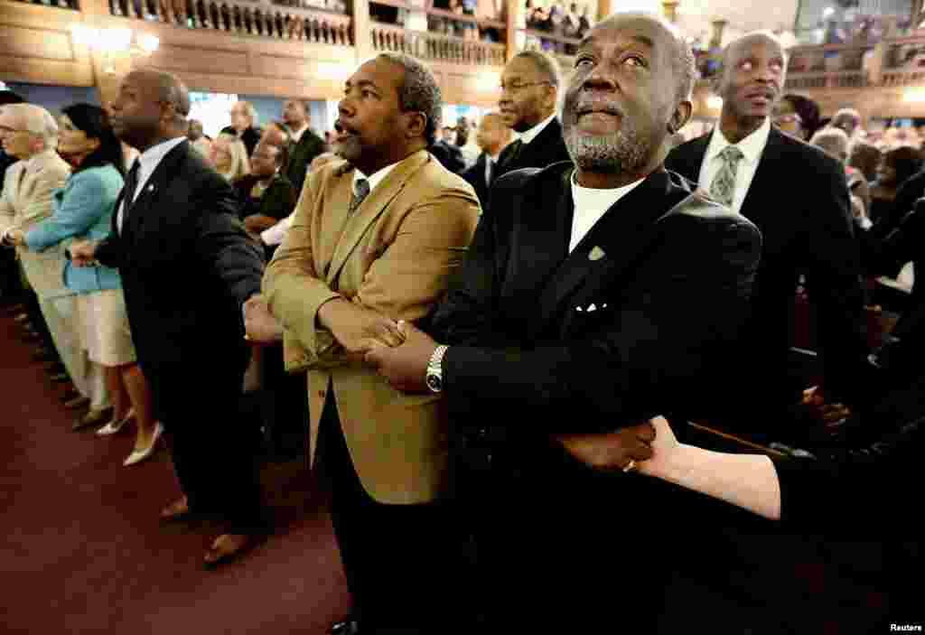 """El reverendo Richard Harkness une sus manos con las del reverendo Jack Lewin mientras los feligreces cantan """"We Shall Overcome"""" en la iglesia Morris Brown AME de Charleston."""