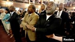 Pendeta Richard Harkness berpegangan tangan dengan pendeta Jack Lewin (dua dari kanan) saat para hadirin menyanyikan lagu pujian dan doa bersama, di gereja Morris Brown AME, Charleston, South Carolina (18/6).