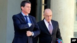French Prime Minister Manuel Valls, left, and interior minister Bernard Cazeneuve, leave the Elysee Palace in Paris after a cabinet meeting, April 22, 2015.
