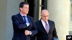 2015年4月22日法国总理曼努埃尔·瓦尔斯(左)和内政部长卡泽纳夫内阁会议后离开爱丽舍宫