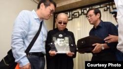 刘晓波遗孀刘霞手捧遗像。刘晓波弟弟刘晓瑄(右)和刘霞弟弟刘晖陪伴(沈阳市政府公布图片)