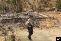 FILE - A Myanmar security officer walks past burned Rohingya houses in Ka Nyin Tan village of suburb Maungdaw, northern Rakhine state of western Myanmar, Sept. 6, 2017.