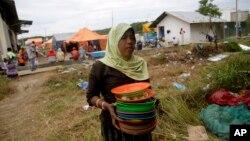 Seorang perempuan migran Rohingya membawa tumpukan piring kotor untuk dicuci di tempat penampungan di Kuala Langsa, Aceh (25/5). (AP/Tatan Syuflana)