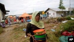 Seorang migran Rohingya di tempat penampungan sementara di Kuala Langsa, Aceh, membawa piring kotor yang digunakan setelah makan utuk dicuci (Foto: dok).