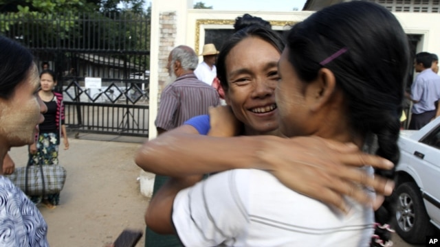 A prisoner, center, is welcomed by her relative outside Insein prison in Rangoon after the government released prisoners, November 15, 2012.
