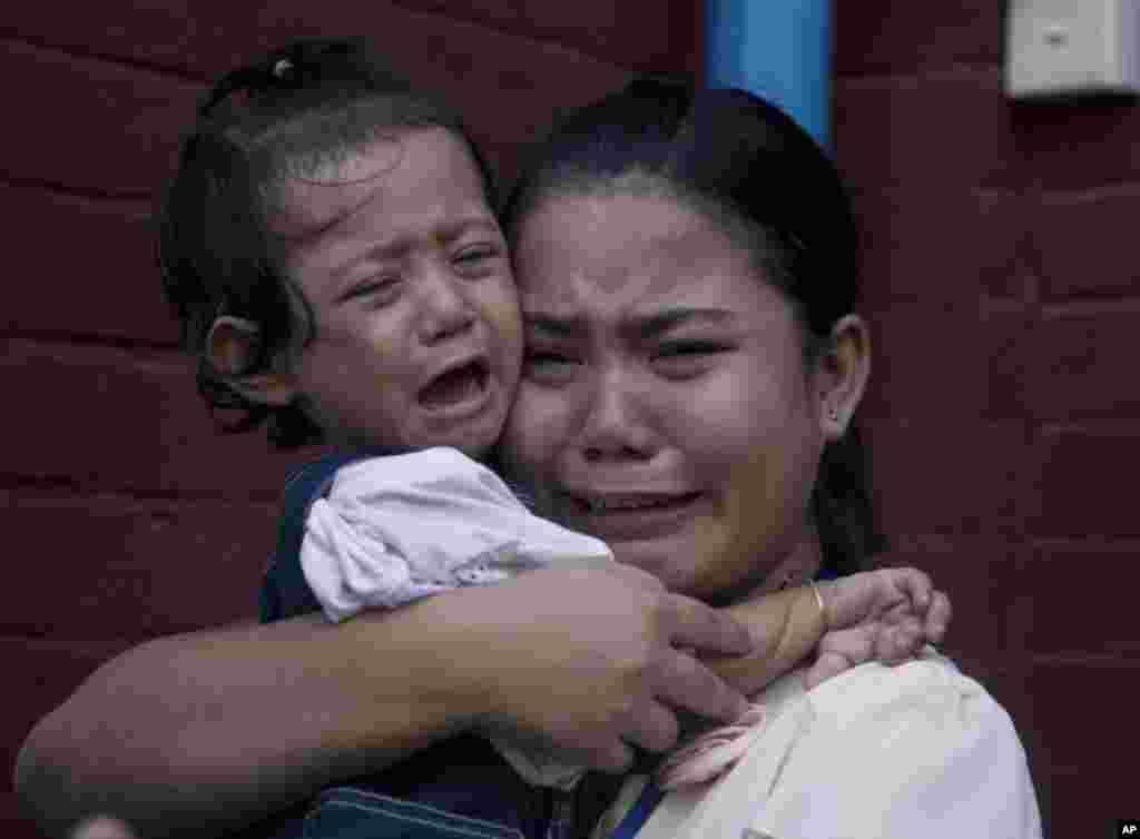 អ្នកស្រី Chit Su Win ប្រពន្ធរបស់អ្នកកាសែត Reuters លោក Kyaw Soe Oo យំបន្ទាប់ជាមួយកូនស្រីនៅខាងក្រៅតុលាការរ៉ង់ហ្គូនប្រទេសមីយ៉ាន់ម៉ា។