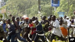 Supporters of Orange Democratic Movement (ODM) run as riot police chase them in Nairobi, Kenya, December 31, 2007.