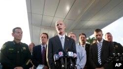 فلوریڈا کے گورنر رک اسکاٹ (درمیان) صحافیوں کو تفصیل بتا رہے ہیں