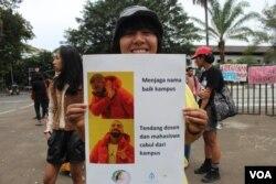 Seorang peserta aksi IWD 2020 menunjukkan poster dalam aksi di Bandung, Minggu, 8 Maret 2020. (Foto: Rio Tuasikal/VOA)