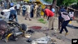 Abantu bariko barahanagura ahaturikiye bombe muri reta ya Maiduguri, Nijeriya, itariki 31/07/2015 .