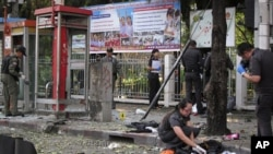 Police and forensic experts investigate the site where a man was injured when a bomb he was carrying exploded, in central Bangkok, Feb. 14, 2012