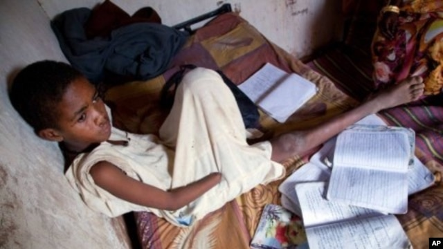 A handout picture released by the United Nations-African Union Mission in Darfur (UNAMID) shows Sudanese Abdulrahim Ahmed Mohammed, 12, sitting in his house at Al-Salam camp for internally displaced people in El-Fasher, the administrative capital of North