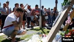 Un homme dépose des bouquets de fleurs à proximité du lieu où une attaque à l'aide d'un camion a causé la mort de plus de 80 personnes en pleine la fête nationale du jour de la Bastille, à Nice, France, 15 juillet 2016. REUTERS / Pascal Rossignol