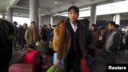 2月1日,在中国南方的东莞市火车东站,民工们载满了行李,排队等待搭载他们回家过新年的列车。