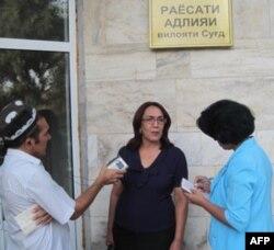 Jurnalistning advokati Fayziniso Voxidova (o'rtada) sud ishini yoritayotgan muxbirlar bilan suhbatda