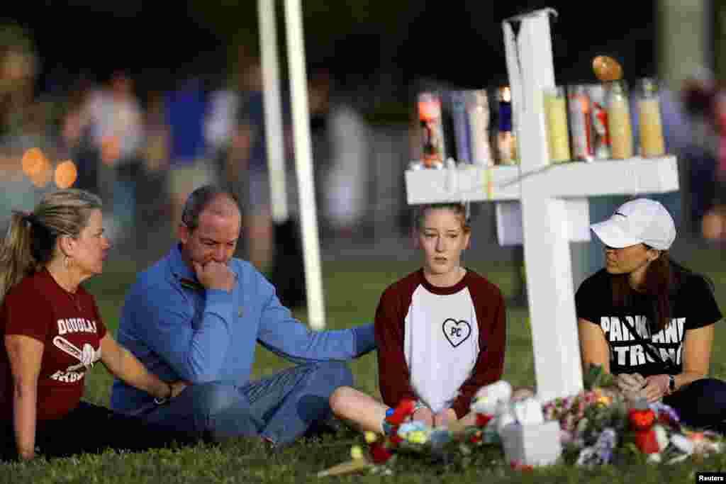 Satu keluarga duduk di sekitar salah satu dari 17 salib di tempat peringatan korban penembakan di SMU Marjory Stoneman Douglas, di Parkland, Florida, 16 Februari 2018.