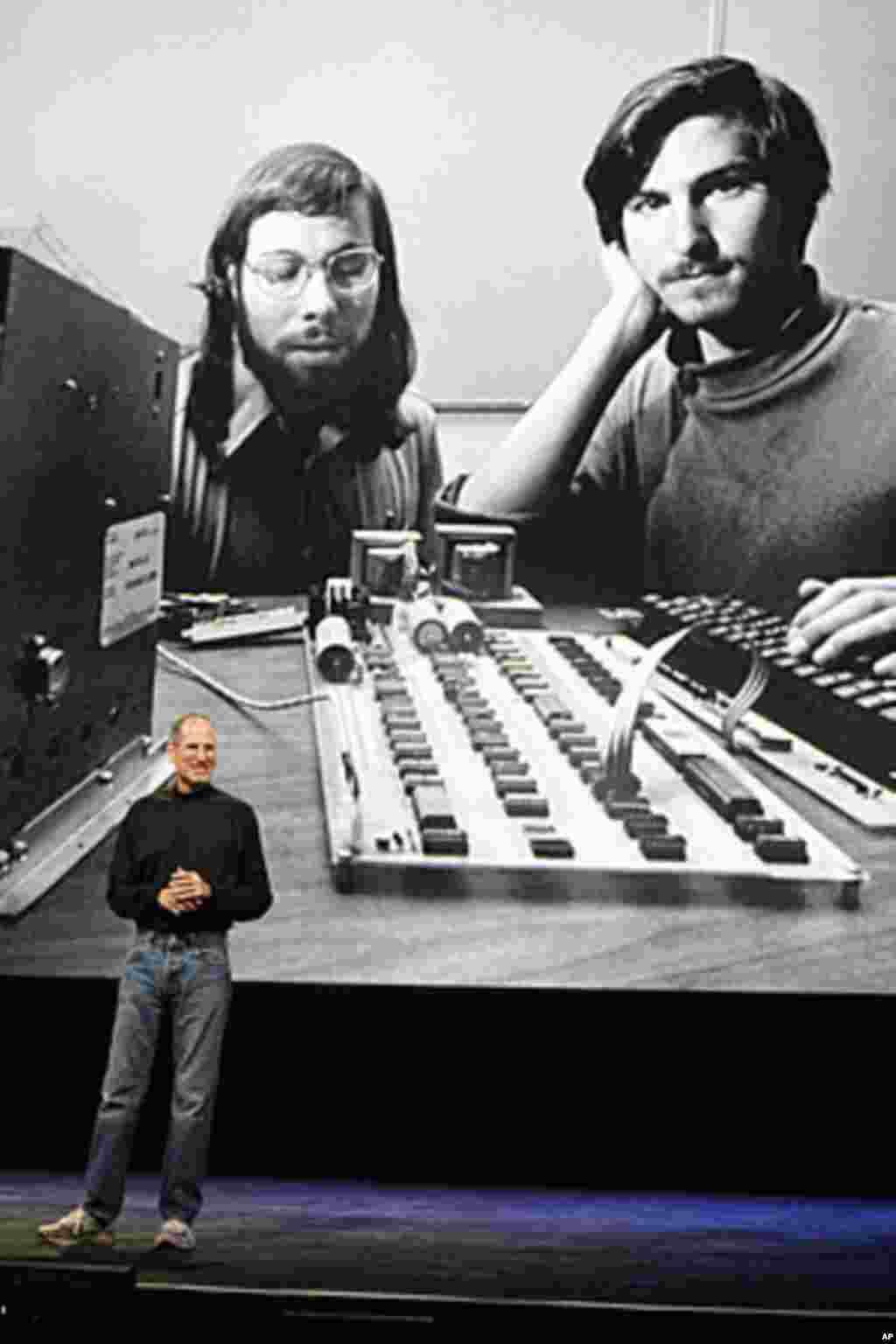 2010年1月27日:在旧金山举行的一次苹果电脑活动中,乔布斯站在一幅巨照下面 - 照片中,年轻的乔布斯(右)与苹果电脑的共同创始人沃兹尼亚克(左)在一起。(AP)