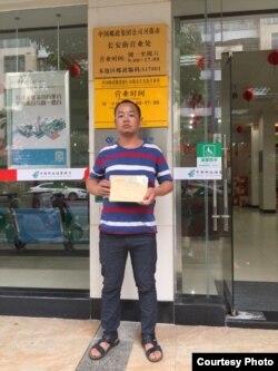 2019年5月30日广东学生家长张国兵在河源市长安街邮局营业处门前准备邮寄信息公开申请信函。(张国兵提供)