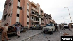 Libyan forces allied with the U.N.-backed government gather in front of ruined buildings at the eastern frontline of fighting with Islamic State militants, in Sirte's neighborhood 650, Libya, Oct. 21, 2016. The six-month fight to oust Islamic State has destroyed much of the city.