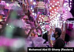 """Seorang pria memeriksa lentera Ramadhan tradisional, yang disebut """"fanous"""", di sebuah kios toko menjelang bulan suci Ramadhan, di tengah pandemi COVID-19 di Kairo, Mesir, 8 April 2021. (Foto: REUTERS/Mohamed Abd El Ghany )"""