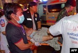 Thai rescue workers transport an injured person after a bomb exploded outside a religious shrine in central Bangkok late on Aug. 17, 2015 killing at least 10 people and wounding scores more.
