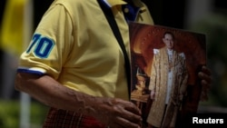 A well-wisher holds a picture of Thailand's King Bhumibol Adulyadej at the Siriraj hospital where he is residing, in Bangkok, Thailand, June 9, 2016.