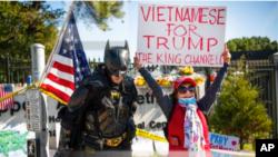 Một người ủng hộ gốc Việt dương biểu ngữ bên ngoài Bệnh viện Quân đội Water Reed nơi Tổng thống Donald Trump điều trị COVID-19 hồi tháng 10/2020. Có nhiều lo ngại Tổng thống Trump sẽ đánh thuế lên hàng hoá Việt Nam theo sau điều tra của USTR về thao túng tiền tệ.