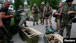우크라이나 정부군이 슬로뱐스크에서 포로로 잡은 반군의 무기를 검사하고 있다.