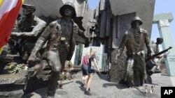Residentes de Varsovia observan el monumento al Levantamiento de Varsovia de 1944 contra la ocupación nazi, en el que murieron unos 18.000 combatientes de la resistencia y 180.000 civiles, en Varsovia, Polonia, el miércoles, 1 de agosto de 2018.