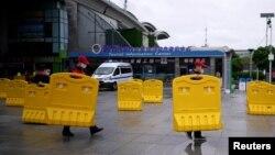 武汉开城第一天,武汉火车站前工人搬走为防疫设置的路障。(2020年3月28日)