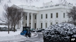 A plow removes snow from the White House driveway after a winter storm, on Tuesday, Feb. 17, 2015, in Washington.