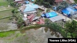 Situasi desa Kayuangin dilihat dari udara yang memperlihatkan salah satu rumah yang roboh akibat gempa bumi. Jumat (28/1/2021). (Foto: VOA/Yoanes Litha)