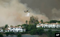 A helicopter drops water on a brush fire behind homes during the Woolsey Fire in Malibu, Calif., Nov. 9, 2018. A fast-moving wildfire in Southern California has scorched a historic movie site and forced numerous celebrities to join the thousands fleeing from the flames.