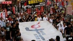 Thousands of people march on a downtown street in Hong Kong Sunday, June 1, 2014, to mark the 25th anniversary of China's bloody crackdown on Tiananmen Square protests on June 4, 1989.