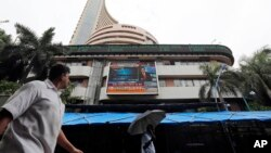 A man looks at the display screen on the facade of the Bombay stock exchange (BSE) in Mumbai, India, July 10, 2014.