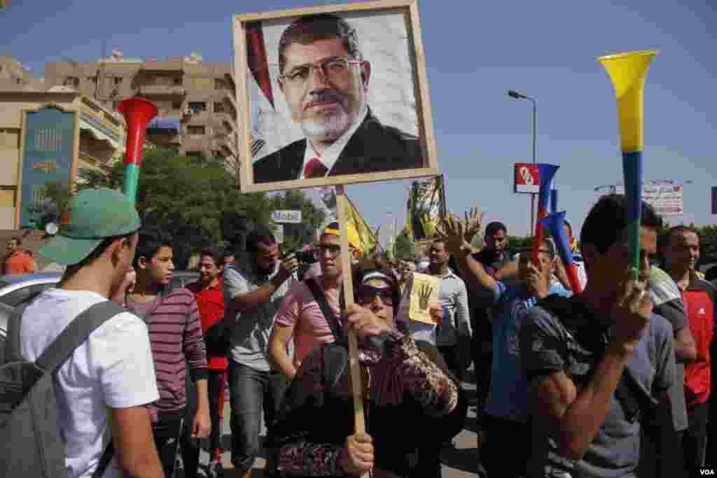 Prosvjednici pokazuju plakat sa slikom zbačenog predsjednika Mohameda Morsija, u Nasr Cityju, u Kairu, 11. oktobra 2013. (Hamada Elrasam for VOA)