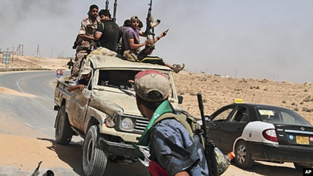 Libyan rebels on their way back from the front line after a six-hour battle in which they succeeded to liberate al-Qawalish, 100 kilometers (60 miles) southwest of Tripoli, July 6, 2011