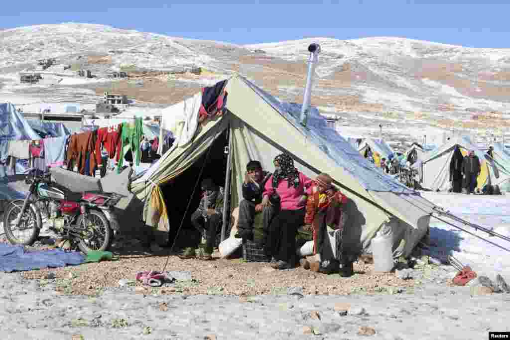 Syrian refugees sit by their tent in a camp on the Lebanese border town of Arsal, Dec. 15, 2013
