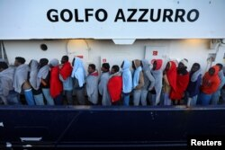 FILE - Migrants line up as they wait to be processed by Italian authorities aboard the former fishing trawler Golfo Azzurro moored in the port of Augusta following their rescue by Spanish NGO Proactiva Open Arms from their drifting dinghies off the Libyan coast in central Mediterranean Sea, April 2, 2017.