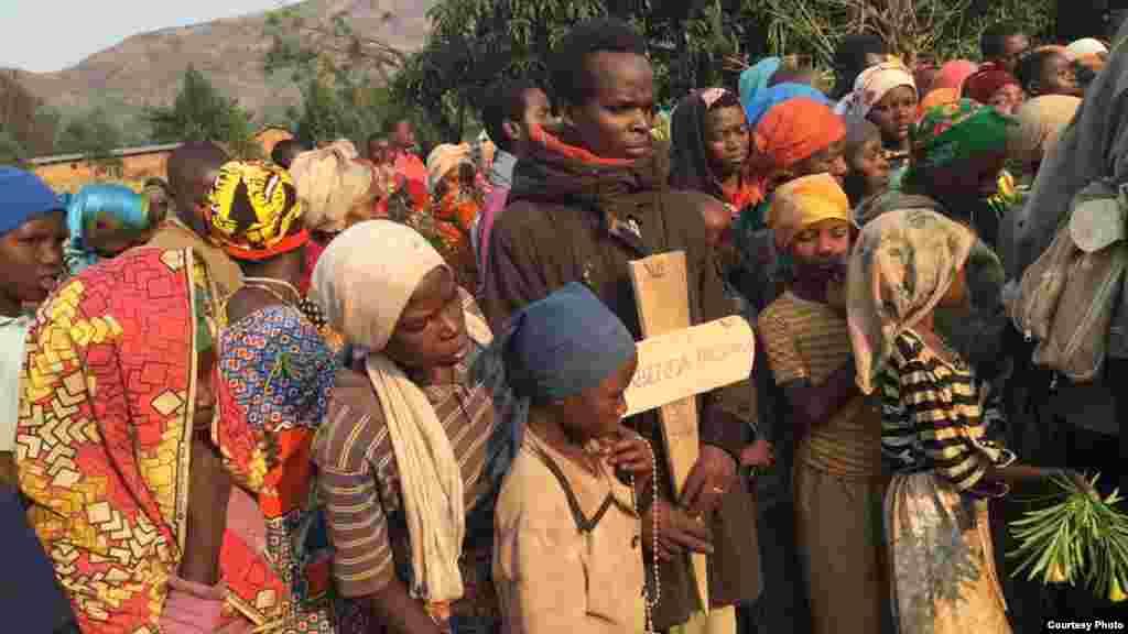 La population burundaise montre des cadavres sur une route, non loin d'une base de la Mission des Nations unies au Congo, le 16 septembre 2017.