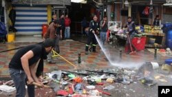 Municipal workers clean up the site of a suicide bombing, one of several explosions that left at least 37 people dead in Baghdad, Feb. 7, 2015.