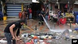 Petugas membersihkan lokasi pemboman bunuh diri di Baghdad (7/2). (AP/Karim Kadim)
