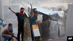 Para demonstran anti-pemerintah menantang polisi anti huru-hara seusai disiram dengan meriam air di Caracas, Venezuela (28/2).