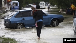 A local resident walks with her child through a flooded street in the southern Russian town of Krymsk July 7, 2012.