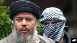 Abu Hamza al-Masri sa maskiranim pripadnikom ličnog obezbeđenja u Londonu, pre osam godina