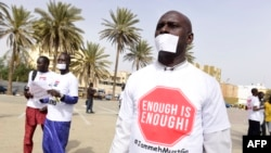 """Des manifestants ont couvert leur bouche avec du papier et portent un t-shirt sur lequel il est marqué """"assez c'est assez"""" à Dakar le 22 avril 2016, contre les violations des droits de l'homme en Gambie."""