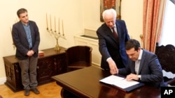 Greece's Prime Minister Alexis Tsipras, right, signs a protocol as the new Greek Finance Minister Euclid Tsakalotos, left, looks on during the swearing in ceremony at Presidential Palace in Athens, Monday, July 6, 2015.